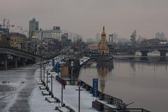 KYIV,乌克兰2017年1月22日:对堤防的早晨视图在内河港附近 城市克里姆林宫横向晚上被反射的河 冬天 免版税库存图片