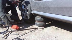 KYIV, ΟΥΚΡΑΝΊΑ - 21 ΑΠΡΙΛΊΟΥ 2019: Το γκρίζο μεταλλικό αυτοκίνητο είναι στο γρύλο για την αντικατάσταση ροδών σε σε αργή κίνηση απόθεμα βίντεο