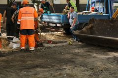 Kyiv/Ουκρανία - 18 μπορούν το 2019: Εργοτάξιο οικοδομής με τους κοινοτικούς εργαζομένους υπηρεσιών στα πορτοκαλιά ομοιόμορφα και  στοκ εικόνα με δικαίωμα ελεύθερης χρήσης