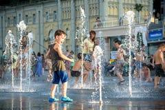 KYIV, ΟΥΚΡΑΝΊΑ ΣΤΙΣ 13 ΑΥΓΟΎΣΤΟΥ 2017: Τα ευτυχή παιδιά έχουν το παιχνίδι διασκέδασης στην πηγή νερού πόλεων την καυτή θερινή ημέ Στοκ Φωτογραφία