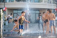 KYIV, ΟΥΚΡΑΝΊΑ ΣΤΙΣ 13 ΑΥΓΟΎΣΤΟΥ 2017: Τα ευτυχή παιδιά έχουν το παιχνίδι διασκέδασης στην πηγή νερού πόλεων την καυτή θερινή ημέ Στοκ Εικόνες