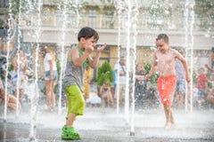 KYIV, ΟΥΚΡΑΝΊΑ ΣΤΙΣ 13 ΑΥΓΟΎΣΤΟΥ 2017: Τα ευτυχή παιδιά έχουν το παιχνίδι διασκέδασης στην πηγή νερού πόλεων την καυτή θερινή ημέ Στοκ εικόνα με δικαίωμα ελεύθερης χρήσης