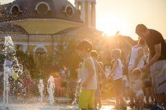 KYIV, ΟΥΚΡΑΝΊΑ ΣΤΙΣ 13 ΑΥΓΟΎΣΤΟΥ 2017: Τα ευτυχή παιδιά έχουν το παιχνίδι διασκέδασης στην πηγή νερού πόλεων την καυτή θερινή ημέ Στοκ Φωτογραφίες