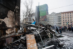 KYIV, УКРАИНА: Стойка людей около, который сгорели баррикад после ночи воюет на занимая улице снега во время бунта стоковые изображения