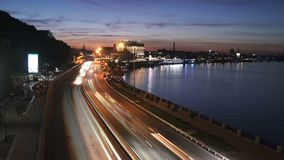 Kyiv city traffic. Kyiv City Cars Traffic Lights Trails alongside the river and sunset sky on the background stock video