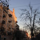 Kyiv city street in winter. Sunset in the old European city street, with a pale moon and a bare tree stock image