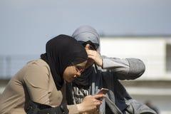 Kyiv de Oekraïne - 21 April, 2018: twee jonge Moslimvrouwen die in zonglazen in smartphone kijken stock foto's