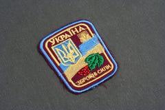 KYIV, de OEKRAÏNE - Juli, 16, 2015 Het Leger eenvormig kenteken van de Oekraïne op gecamoufleerde eenvormig stock fotografie