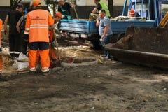 Kyiv/de Oekra?ne - 18 kunnen 2019: Bouwwerf met communale de dienstarbeiders in oranje eenvormige en bouwmachines royalty-vrije stock afbeelding