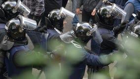 KYIV, DE OEKRAÏNE - OCT 17, 2017: Detachement van politieagenten in helmen die zich achter elkaar langs de straat bewegen stock videobeelden