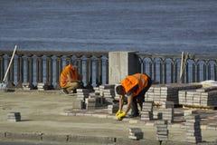 Kyiv de Oekraïne - 21 04 2018: twee arbeiders in oranje eenvormige het herstellen brugweg met concrete betonmolen stock foto