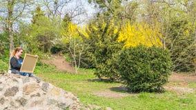 04 23 2019 - Kyiv, de Oekra?ne Botanische Tuin in het centrum van de hoofdstad van de Oekra?ne De vrouw trekt in het park stock afbeelding