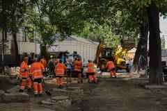 Kyiv/de Oekra?ne - 18 kunnen 2019: Bouwwerf met communale de dienstarbeiders in oranje eenvormige en bouwmachines stock foto
