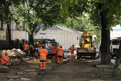 Kyiv/de Oekra?ne - 18 kunnen 2019: Bouwwerf met communale de dienstarbeiders in oranje eenvormige en bouwmachines stock foto's
