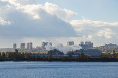 View on industrial city of Kyiv. Kyiv landscape with view on river, functioning plant, multi-storey buidings and gorgeous sky. Industrial city and urban life royalty free stock photo