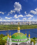 Kyiv-Pechersk Lavra. The dome of a temple against the residential neighborhoods of the city and the sky with clouds. Kyiv-Pechersk Lavra, Ukraine Stock Photo