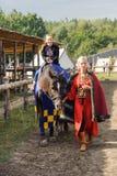 Kyiv region, UA, 24-09-2011 dziecko siedzi na koniu, costumed kobieta pomaga Kostiumowy odtwarzanie park Kyivan Rus średniowieczn Obrazy Stock