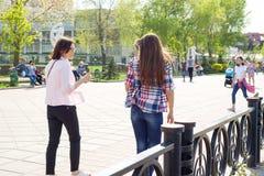 Kyiv, UA, 29-04-2018 Żeńscy przyjaciele chodzą puszek i opowiadają ulica drzewo pola Zdjęcie Stock