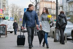 Kyiv UA, 17-04-2019 Το υπαίθριο πορτρέτο του νέου ζεύγους που περπατά με τη βαλίτσα στην οδό πόλεων, ο ευτυχείς νεαρός άνδρας και στοκ φωτογραφία με δικαίωμα ελεύθερης χρήσης
