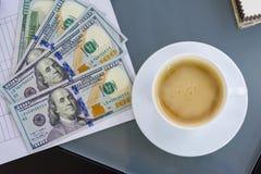 Kyiv UA, 24-04-2018 En la taza del dinero del contrato de la tabla de café, visión superior Fotografía de archivo
