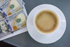 Kyiv UA, 24-04-2018 En la taza del dinero del contrato de la tabla de café, visión superior Imagen de archivo libre de regalías