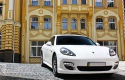 Kyiv, Ucrânia, o 25 de junho de 2015; Porsche branco Porsche Panamera no fundo de construções bonitas imagens de stock royalty free