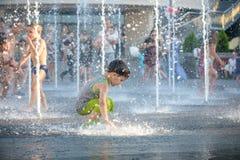 KYIV, UCRÂNIA 13 DE AGOSTO DE 2017: As crianças felizes têm o divertimento que joga na fonte de água municipal no dia de verão qu Fotos de Stock Royalty Free