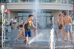 KYIV, UCRÂNIA 13 DE AGOSTO DE 2017: As crianças felizes têm o divertimento que joga na fonte de água municipal no dia de verão qu Imagens de Stock Royalty Free