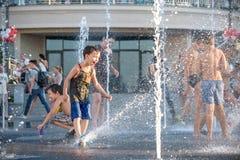 KYIV, UCRÂNIA 13 DE AGOSTO DE 2017: As crianças felizes têm o divertimento que joga na fonte de água municipal no dia de verão qu Foto de Stock Royalty Free