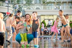 KYIV, UCRÂNIA 13 DE AGOSTO DE 2017: As crianças felizes têm o divertimento que joga na fonte de água municipal no dia de verão qu Imagens de Stock