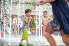KYIV, UCRÂNIA 13 DE AGOSTO DE 2017: As crianças felizes têm o divertimento que joga na fonte de água municipal no dia de verão qu Fotografia de Stock