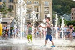 KYIV, UCRÂNIA 13 DE AGOSTO DE 2017: As crianças felizes têm o divertimento que joga na fonte de água municipal no dia de verão qu Foto de Stock