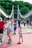 Kyiv, Ucr?nia - 18 de maio de 2019 Ponte do parque sobre o rio de Dnipro Povos que andam ao longo da ponte pedestre no fim de sem fotografia de stock royalty free