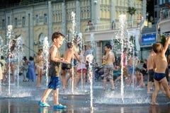 KYIV, UCRAINA 13 AGOSTO 2017: I bambini felici si divertono il gioco in fontana della città il giorno di estate caldo Fotografia Stock Libera da Diritti