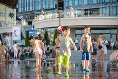 KYIV, UCRAINA 13 AGOSTO 2017: I bambini felici si divertono il gioco in fontana della città il giorno di estate caldo Fotografie Stock Libere da Diritti