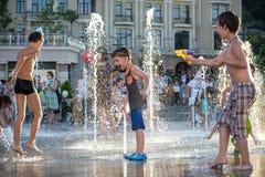 KYIV, UCRAINA 13 AGOSTO 2017: I bambini felici si divertono il gioco in fontana della città il giorno di estate caldo Fotografie Stock