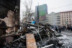 KYIV, UCRAINA: Il supporto della gente vicino alle barriere bruciate dopo la notte combatte sulla via d'occupazione della neve dur Immagini Stock