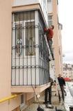 KYIV, UCRAINA - 3 novembre 2017: Appaltatori che installano le barre di sicurezza del ferro della finestra immagine stock libera da diritti