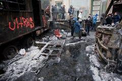KYIV, UCRANIA: El paseo de la gente más allá de la calle del invierno con los autobuses hielo-cubiertos quemó en luchas con los pe Fotos de archivo libres de regalías