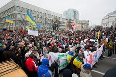 KYIV, UCRANIA: Muchedumbre enorme de hombres y de mujeres con diversos bunners antigubernamentales que caminan abajo de la calle d Fotos de archivo