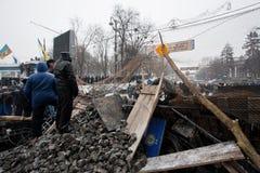 KYIV, UCRANIA: Pelotón de la policía del reloj de la gente detrás de las barricadas con los ladrillos y de la madera durante prote Imagen de archivo libre de regalías