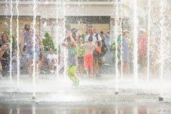 KYIV UKRAINA AUGUSTI 13, 2017: Lyckliga ungar har gyckel som spelar i stadsvattenspringbrunn på varm sommardag Fotografering för Bildbyråer