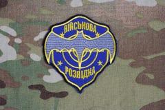 KYIV UKRAINA - Juli, 16, 2015 Ukraina \ 'enhetligt emblem för s-militär underrättelse på den kamouflerade likformign arkivfoto