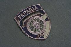 KYIV UKRAINA - Juli, 16, 2015 Tillståndsräddningstjänst av Ukraina det enhetliga emblemet på den kamouflerade likformign arkivfoton