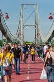 Kyiv Ukraina - Maj 18, 2019 Parkera bron ?ver den Dnipro floden Folk som promenerar den fot- bron p? helg arkivbild