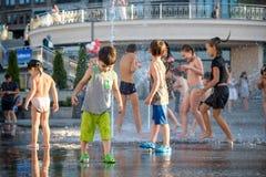 KYIV, UKRAINA SIERPIEŃ 13, 2017: Szczęśliwi dzieciaki zabawę bawić się w wody miejskiej fontannie na gorącym letnim dniu Zdjęcia Stock