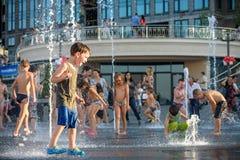 KYIV, UKRAINA SIERPIEŃ 13, 2017: Szczęśliwi dzieciaki zabawę bawić się w wody miejskiej fontannie na gorącym letnim dniu Obrazy Stock