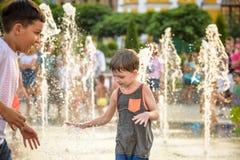 KYIV, UKRAINA SIERPIEŃ 13, 2017: Szczęśliwi dzieciaki zabawę bawić się w wody miejskiej fontannie na gorącym letnim dniu Fotografia Stock