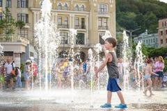KYIV, UKRAINA SIERPIEŃ 13, 2017: Szczęśliwi dzieciaki zabawę bawić się w wody miejskiej fontannie na gorącym letnim dniu Zdjęcie Royalty Free