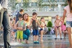 KYIV, UKRAINA SIERPIEŃ 13, 2017: Szczęśliwi dzieciaki zabawę bawić się w wody miejskiej fontannie na gorącym letnim dniu Obraz Stock